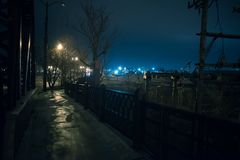 Urban steel factory wasteland scenery in Chicago at night. Urban steel factory wasteland scenery in urban Chicago with a dark vintage bridge sidewalk and a huge royalty free stock image
