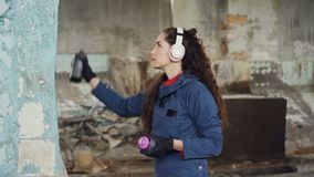 Urban street artist in headphones is listening to music and painting on the wall in old empty house. Pretty girl is. Urban street artist in wireless headphones stock video