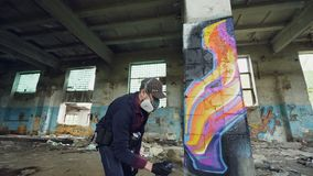 Urban street artist is painting graffiti in abandoned building with dirty walls and windows, he is using paint spray. Urban street artist is painting graffiti in stock video