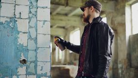 Urban street artist is standing near damaged column inside empty building and painting using aerosol paint spray. Modern. Urban street artist is standing near stock video footage