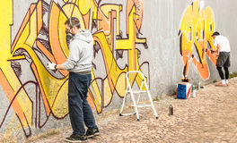 Urban street artists painting colorful graffiti on generic wall Royalty Free Stock Image