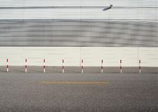 Urban street background. White and red roadside poles on asphalt road in front of a white wall made of aluminium panels.  royalty free stock photo