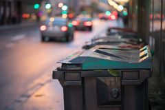 Garbage cans and street lights in urban city, evening. Urban street life with garbage container and street lights can rubbish waste plastic recycling city stock image
