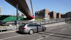 Urban street with modern suspension footbridge. And vehicle traffic stock video footage