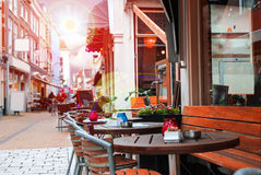 Urban street with a picturesque cafe in rays sun Royalty Free Stock Photos