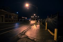 Urban street scenery at night. Urban street scenery with an industrial factory and a city street leading to a vintage bridge in Chicago at night Royalty Free Stock Photo