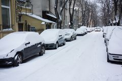 Urban street after snow storm. Cars covered with snow Royalty Free Stock Photo