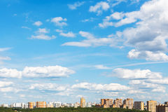 Urban street under blue sky with fluffy clouds Stock Images
