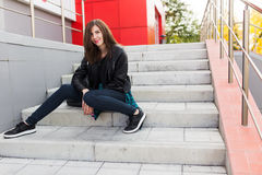Urban student girl posing in a leather jacket outdoors in the city Royalty Free Stock Photography
