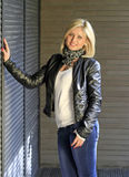 Urban style. Blond woman dressed in leather jacket and blue jeans Stock Photography
