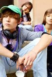 Urban style. Cute guy in casual clothes looking aside on background of two girls Royalty Free Stock Image