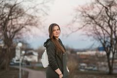 Urban style and fashion concept. Outdoor portrait of beautiful stylish young European female model with long brown hair. Wearing trendy hoodie and white Royalty Free Stock Photos