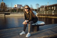 Urban style and fashion concept. Outdoor portrait of beautiful stylish young European female model with long brown hair. Wearing trendy hoodie, sunglasses Stock Photography