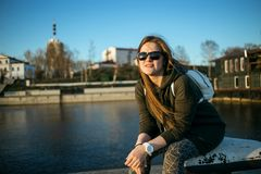 Urban style and fashion concept. Outdoor portrait of beautiful stylish young European female model with long brown hair. Wearing trendy hoodie, sunglasses and Stock Photography