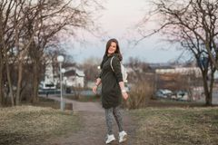 Urban style and fashion concept. Outdoor portrait of beautiful stylish young European female model with long brown hair. Wearing trendy hoodie and white Royalty Free Stock Photography