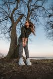 Urban style and fashion concept. Outdoor portrait of beautiful stylish young European female model with long brown hair. Wearing trendy hoodie and white Royalty Free Stock Photo