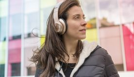 Urban style, girl in the street listening to music with headphon. Es on her head, she wears a long hair to the wind and winter jacket Royalty Free Stock Photos