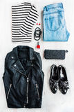 Urban style woman collage clothing. Top view of a leather jacket, striped blouse, jeans and accessories. Stock Image