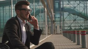 Urban styled businessman talking on smartphone while sitting at the airport and waiting for a flight. Casual young. Businessman wearing suit jacket and shoulder stock video footage