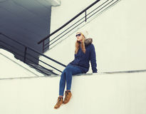 Urban stylish hipster girl outdoors sitting. In the city royalty free stock images