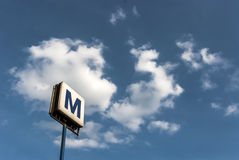 Urban subway sign on blue sky. Urban subway sign with white clouds on blue sky in the background in Bucharest, Romania Stock Photo