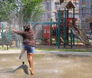 Urban Summer. Girl jumping through spray pool in an urban playground Stock Images