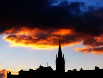 Urban sunset. With church-tower and rooftops in foreground and orange clouds Royalty Free Stock Image