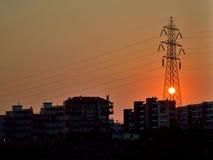 Urban Sunset behind High Voltage Pole. Urban scene sunset in the center of a high voltage pole royalty free stock image