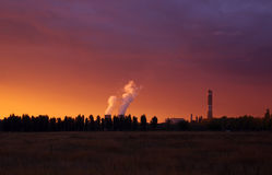 Urban  sunset. Sunset over urban industrial landscape and power plant polluting the enviromen Royalty Free Stock Photo