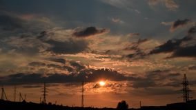 Sunset with power lines on background. Urban sunset with sillhoutte civilization Stock Photo