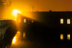Urban sunset. Some buildings and a bridge reflected on the river during a foggy sunset stock photography