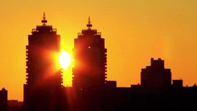 Urban sunset. Sun set down between two buildings stock footage