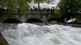 Urban Surfers on a man-made wave on the Eisbach river in the center of Munich, Germany. MUNICH, GERMANY, SEPTEMBER 15, 2017: Urban Surfers on a man-made wave on stock video footage