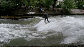 Urban surfers ride the standing wave on the Eisbach River, Munich, Germany. Slow Motion. MUNICH, GERMANY, SEPTEMBER 15, 2017: Urban surfers ride the standing stock video footage