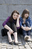 Urban teen girls sitting at stone wall Stock Image