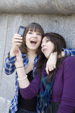 Urban teen girls taking photo by mobile phone Stock Photos