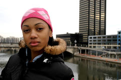 Urban teen looks at the city. Young African American teen looks at the city while standing on a bridge stock photo