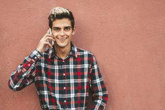 Urban teen portrait. Teen boy on cellphone leaning against wall smiling while on a cellphone in urban outdoor portrait Stock Image