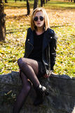 Urban teenage girl with sunglasses  posing in a leather jacket Stock Images