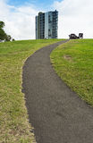 Path to the top. Pathway receding up grassy hillside with high rise urban tower block in background. Copyspace Royalty Free Stock Photography