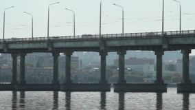 Urban traffic on the bridge. Urban traffic goes across the bridge over the river in the city stock footage