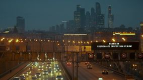 Urban traffic on the highway, against the backdrop of skyscrapers. Translation: the driver, observe the speed limit stock footage