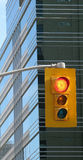Urban traffic light. Traffic signal or stop light near a large urban office building Royalty Free Stock Photography
