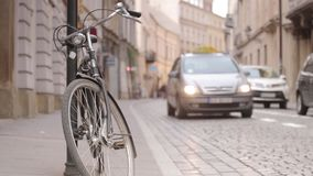 Urban traffic - pedestrians, cars and bicycle on historic street. Of Krakow, Poland stock video