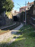 Urban train rails that pass through downtown. The ruins of the train tracks run along the tunnel and surround the buildings and the grass Stock Photos
