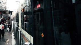 Urban tram approaching to the station, passengers passing through a turnstile in Eskisehir, Turkey. Eskisehir, Turkey - March 13, 2017: Modern tramway stock footage