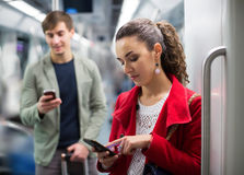 Urban transport scene: couple with cell phones Stock Image