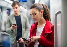 Urban transport scene: couple holding phones Royalty Free Stock Image