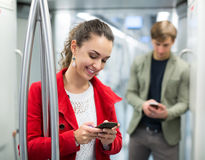 Urban transport scene: people with cell phones. And smiling underground Stock Photo