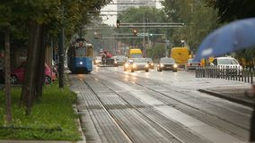 Urban transportation, view of blue tram and cars driving on the road, evening. Stock footage stock video